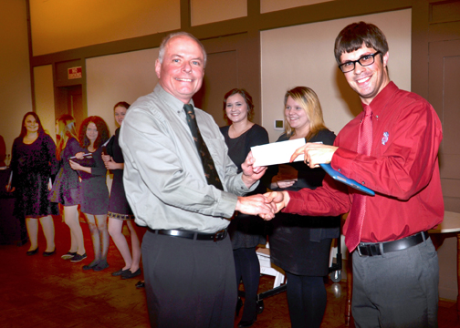 Ray Jacobson presents check to Badger H.S. for their singing at the Christmas Party.